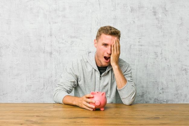 Giovane uomo risparmiando soldi con un salvadanaio divertirsi coprendo metà del viso con il palmo.