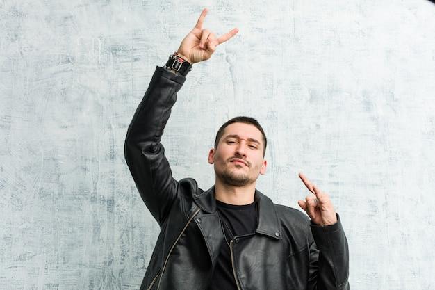 Giovane uomo rocker che celebra un giorno speciale, salta e alza le braccia con energia.