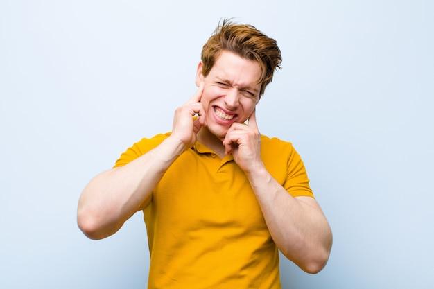 Giovane uomo rosso che sembra arrabbiato, stressato e infastidito, che copre entrambe le orecchie per un rumore assordante, suono o musica ad alto volume sulla parete blu