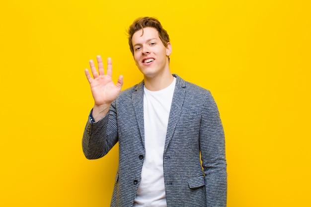 Giovane uomo rosso che sorride allegramente e allegramente, agitando la mano, dandovi il benvenuto e salutandovi
