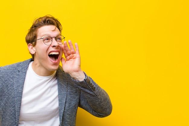 Giovane uomo rosso che urla ad alta voce e con rabbia a copyspace sul lato, con la mano accanto alla bocca arancione