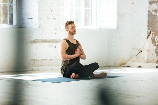 Giovane uomo schietto che si siede su una stuoia di forma fisica
