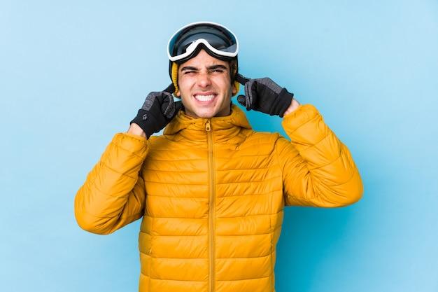 Giovane uomo sciatore che indossa occhiali da snowboard che coprono le orecchie con le mani.