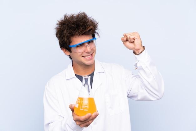 Giovane uomo scientifico sopra la parete blu isolata che fa forte gesto