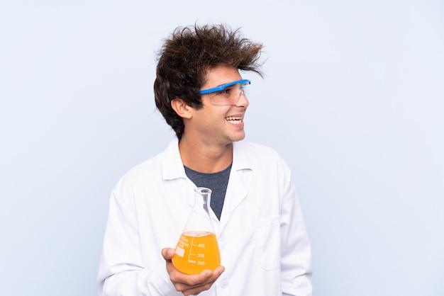 Giovane uomo scientifico sopra la parete blu isolata che osserva al lato