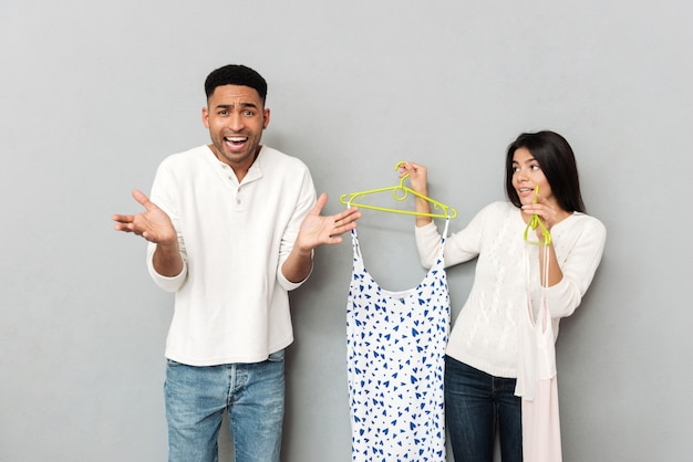 Giovane uomo scontento in piedi vicino a donna con abiti