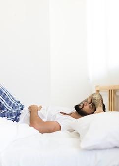 Giovane uomo sdraiato sul letto