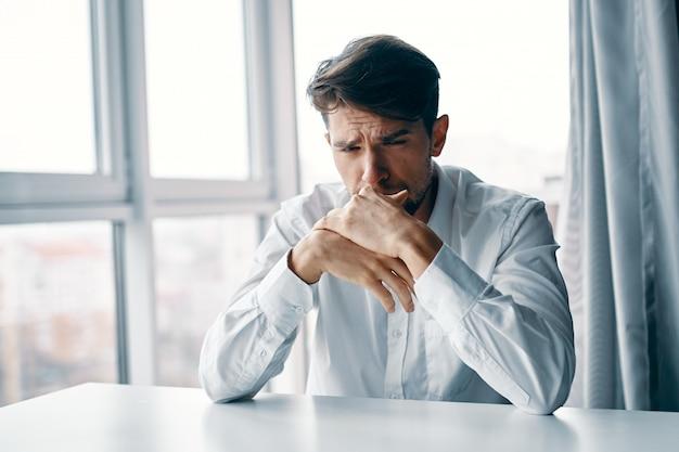 Giovane uomo seduto a un tavolo depresso sullo sfondo di una finestra