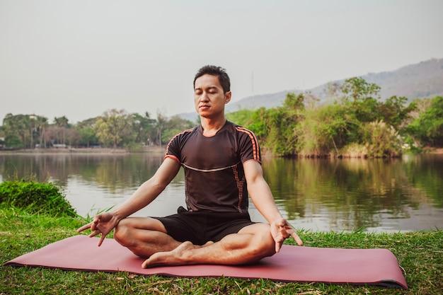 Giovane uomo seduto e meditare