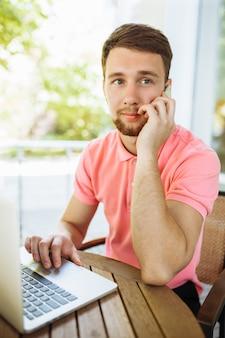 Giovane uomo seduto in un caffè sulla strada, all'aperto con il portatile e parlando al telefono