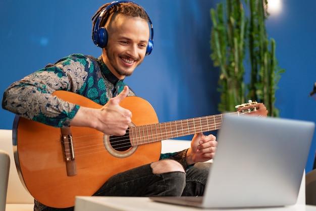Giovane uomo seduto nella sua stanza e guardare il tutorial di chitarra sul portatile
