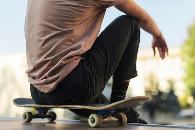 Giovane uomo seduto su uno skateboard