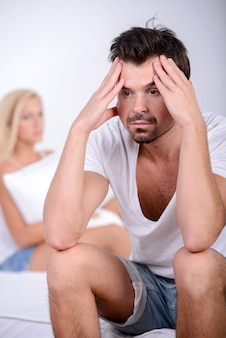 Giovane uomo seduto sul letto, contro la moglie arrabbiata.