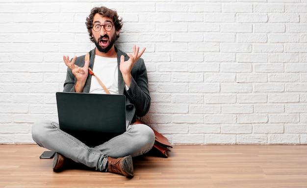 Giovane uomo seduto sul pavimento che grida con uno sguardo pazzo e stupito di sorpresa