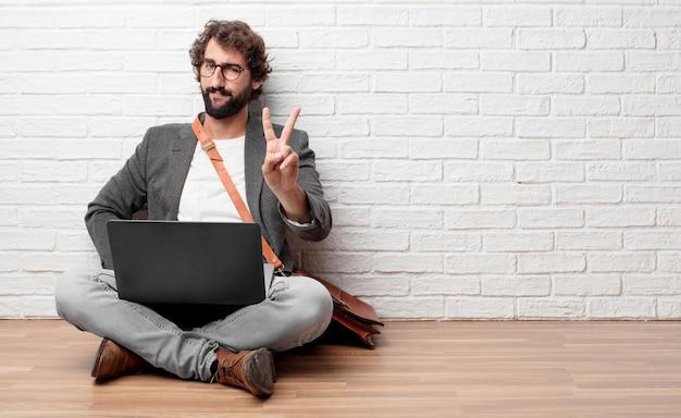 Giovane uomo seduto sul pavimento con un'espressione orgogliosa, felice e sicura