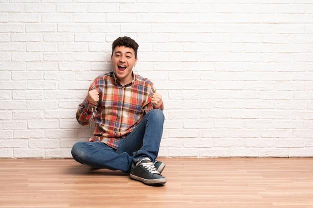 Giovane uomo seduto sul pavimento per celebrare una vittoria nella posizione del vincitore