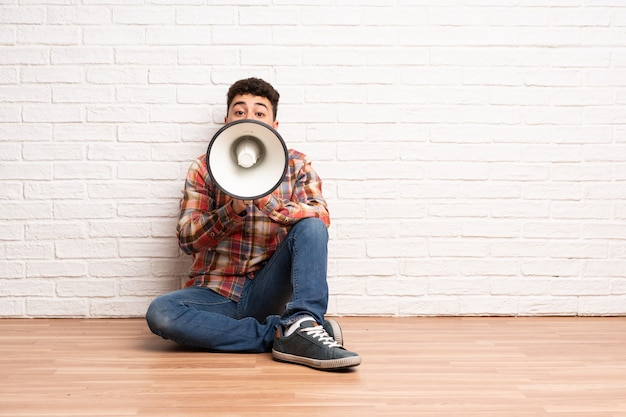Giovane uomo seduto sul pavimento urlando attraverso un megafono
