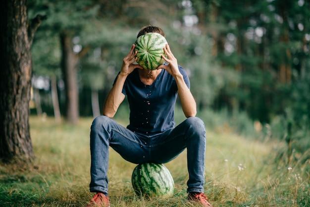 Giovane uomo seduto sull'anguria e nascondendo il viso dietro l'anguria nelle sue mani