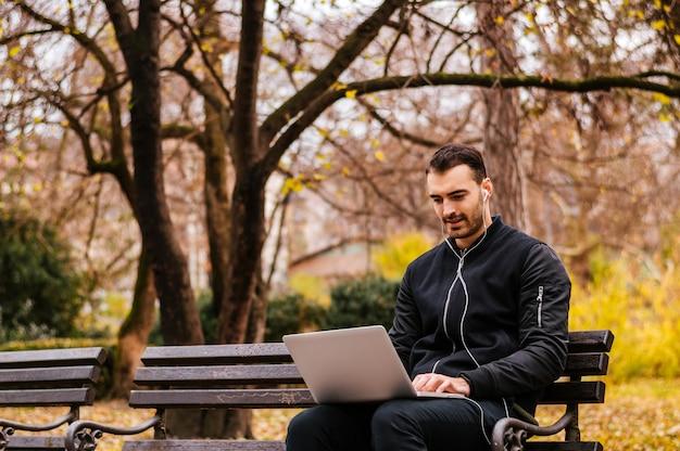 Giovane uomo seduto sulla panchina con il portatile in grembo.