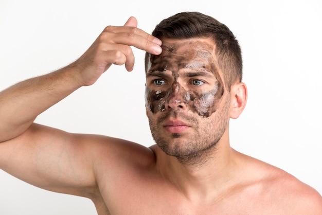 Giovane uomo senza camicia che applica maschera nera sul fronte