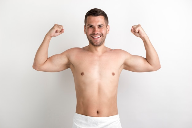 Giovane uomo senza camicia che flette i suoi muscoli contro la parete bianca
