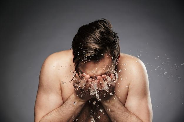 Giovane uomo senza camicia del ritratto che lava il suo fronte con acqua