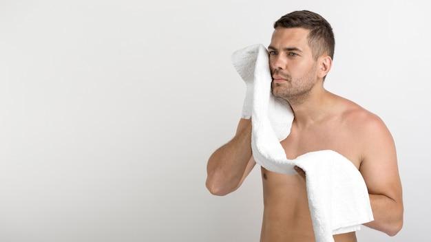 Giovane uomo senza camicia serio che pulisce il suo fronte con l'asciugamano che sta contro il fondo bianco