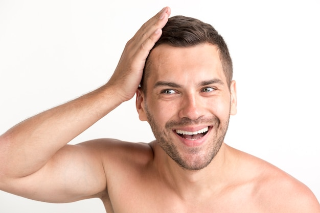 Giovane uomo senza camicia sorridente che tocca i suoi capelli sopra il contesto bianco