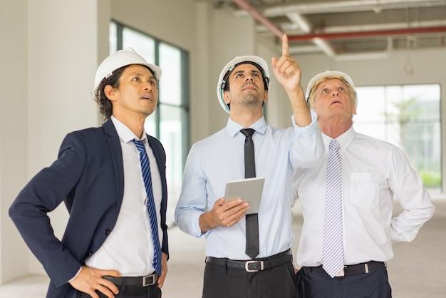 Giovane uomo serio in casco e cravatta con tavoletta scortato con due ingegneri
