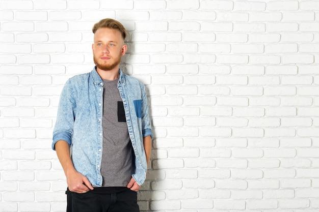 Giovane uomo sexy contro un muro di mattoni bianco
