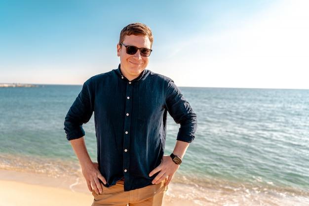 Giovane uomo sicuro sulla spiaggia dell'oceano. libero professionista felice. vacanze estive spagna, barcellona