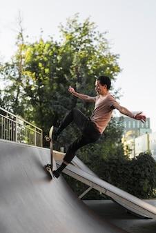 Giovane uomo skateboard in strada
