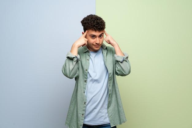Giovane uomo sopra blu e verde, avendo dubbi e pensieri