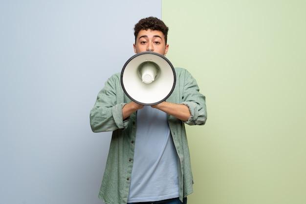Giovane uomo sopra gridare blu e verde attraverso un megafono
