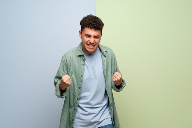 Giovane uomo sopra la parete blu e verde frustrato da una brutta situazione