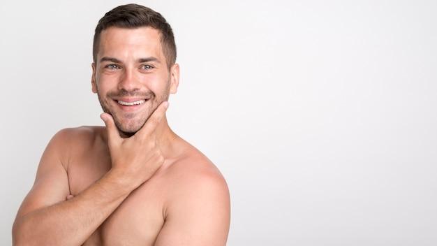Giovane uomo sorridente bello che esamina macchina fotografica e che tiene mano sul mento mentre stando contro la parete bianca