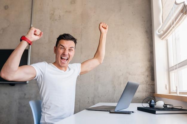 Giovane uomo sorridente bello in vestito casual che si siede al tavolo che lavora al computer portatile, libero professionista a casa, che tiene le mani in alto nel successo