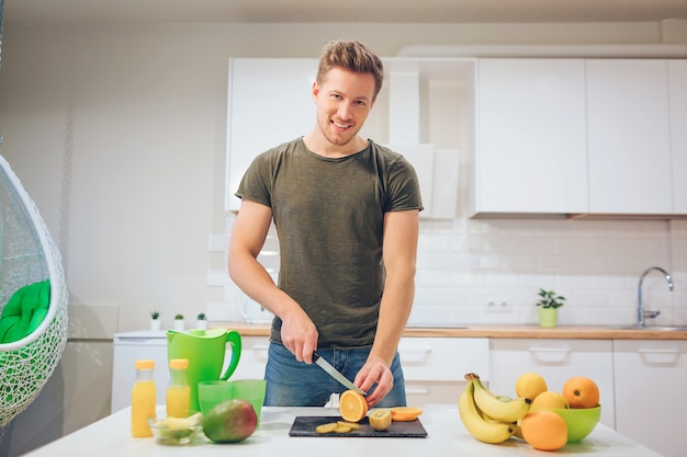 Giovane uomo sorridente che cucina frutta fresca nella cucina. cibo salutare. pasto vegetariano. disintossicazione dietetica
