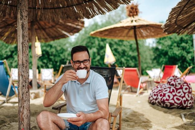 Giovane uomo sorridente che gode del caffè in spiaggia.