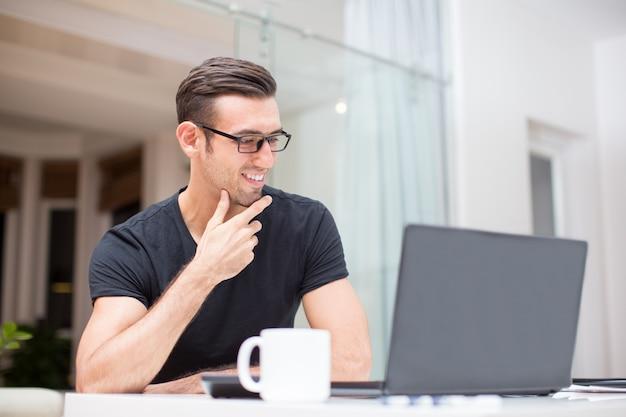 Giovane uomo sorridente che lavora al computer portatile a casa