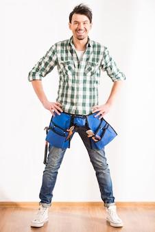 Giovane uomo sorridente con gli strumenti per la riparazione domestica.