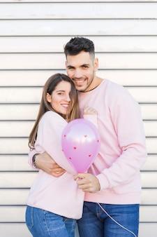 Giovane uomo sorridente con palloncino abbracciando attraente donna felice