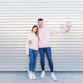 Giovane uomo sorridente con palloncino che abbraccia donna attraente