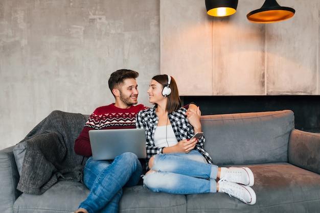 Giovane uomo sorridente e donna seduta a casa in inverno, lavorando al computer portatile, tenendo lo smartphone, ascoltando le cuffie, coppia nel tempo libero che trascorre del tempo online, libero professionista, incontri