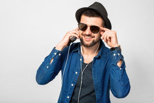 Giovane uomo sorridente felice bello che ascolta la musica in auricolari isolati su sfondo bianco studio, tenendo lo smartphone, indossa una camicia di jeans, cappello e occhiali da sole