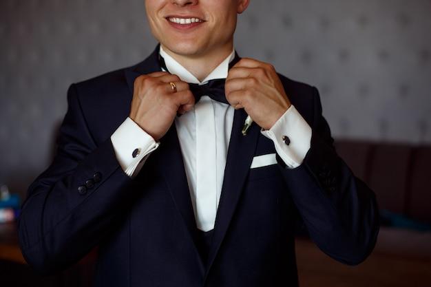 Giovane uomo sorridente in camicia bianca e abito nero regola la farfalla da vicino. ragazzo alla moda mette un tailleur. mattina degli sposi vicino