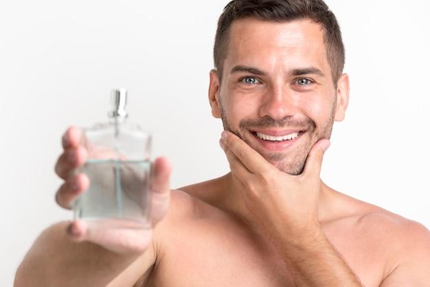Giovane uomo sorridente senza camicia che mostra la bottiglia dello spruzzo della lozione dopobarba