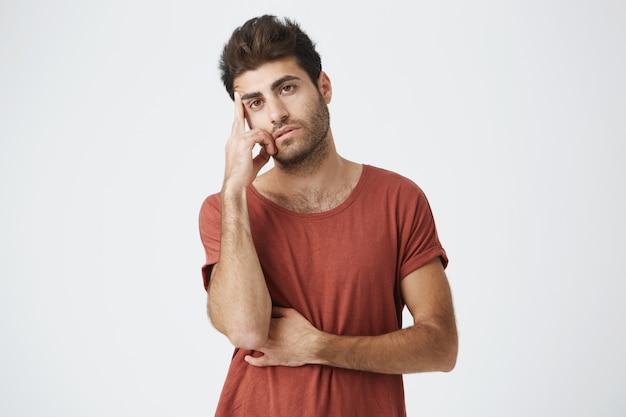 Giovane uomo spagnolo alla moda dalla pelle scura infelice in maglietta rossa che tiene la mano sulla fronte che sembra stanca e annoiata dopo la lunga giornata nell'unità.