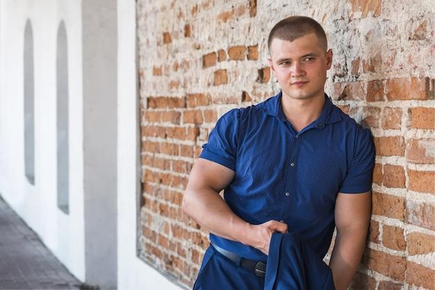 Giovane uomo sportivo bello in un tailleur blu su uno sfondo di un muro di mattoni in estate.