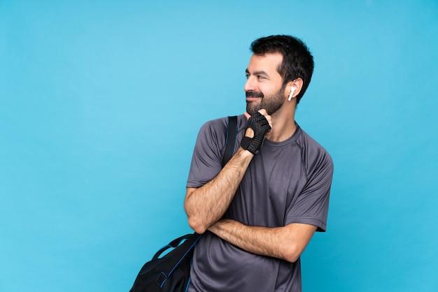 Giovane uomo sportivo con la barba che guarda al lato